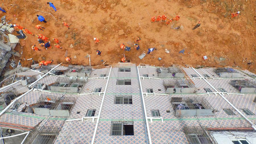 Китайские спасатели работают на месте оползня в Шэньчжэнь на 21 декабря, 2015.