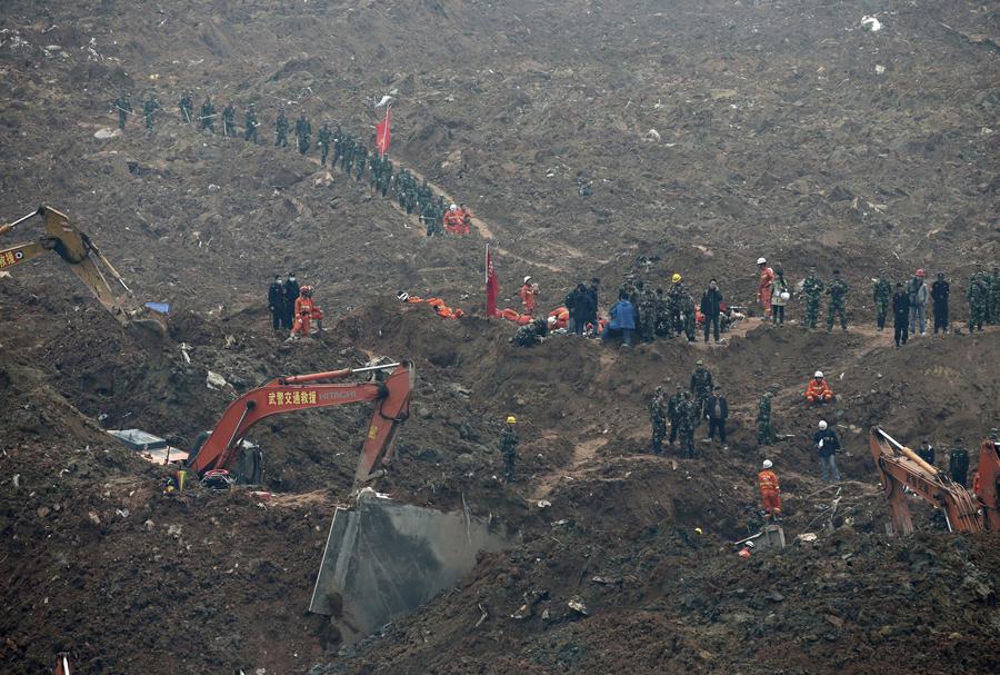 Спасатели использовать технику для поиска выживших которые погребены под морем красных шламов в Шэньчжэне, 21 декабря, 2015.