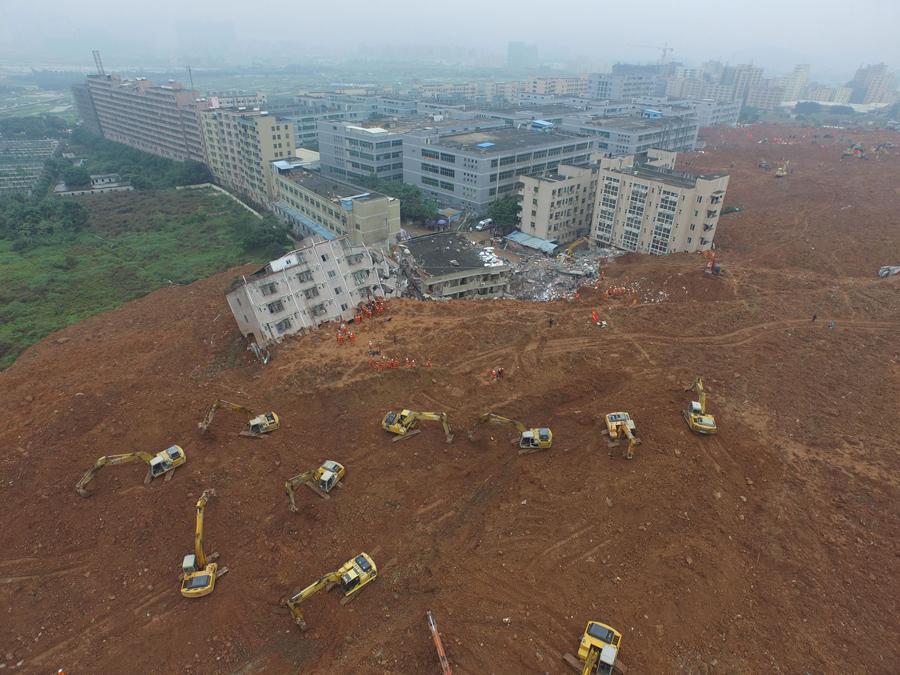 Экскаваторы работают на месте оползня для поиска выживших среди обломков разрушенных зданий в Шэньчжэне 21 декабря, 2015.