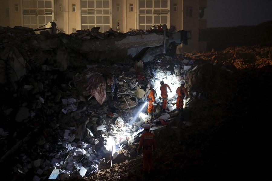 Пожарные с фонариками ищут выживших среди обломков разрушенных зданий после оползня в Шэньчжэне, 20 декабря 2015.