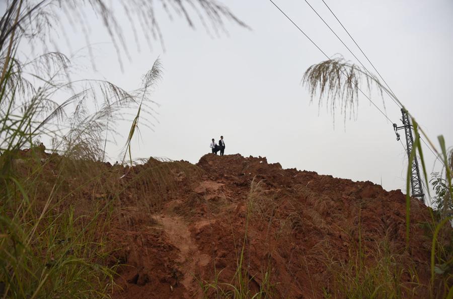Мужчины в деловых костюмах стоят на куче грязи после оползня в Шэньчжэне, 21 декабря, 2015.