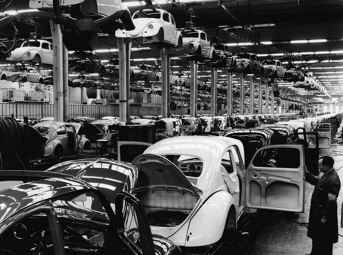 An employee at a Volkswagen plant work inspects a Volkswagen 1200 Sedan, better known as a Beetle, on the assembly line, Wolfsburg, Germany, 1960s. (Photo by Pictorial Parade/Getty Images)