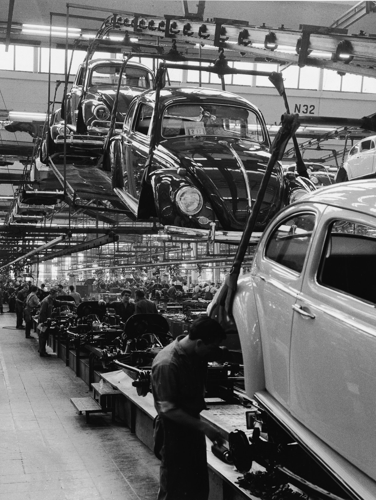 Employees at a Volkswagen plant work on an assembly line to complete Volkswagen 1200 Sedans, better known as Beetles, Wolfsburg, Germany, 1960s. In the foreground, a man guides a car's body as it is lowered onto the chassis. (Photo by Pictorial Parade/Getty Images)