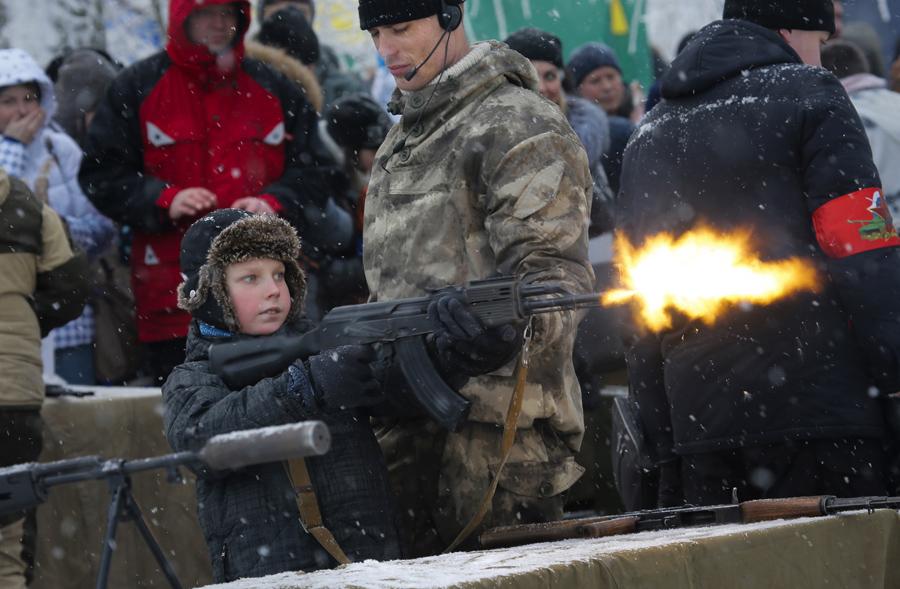 Инструктор помогает мальчику стрелять из оружия заряженного холостыми патронами на выставке во время военного шоу в Санкт-Петербург, Россия, 17 января 2016.