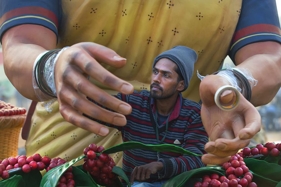 Индийский рабочий красит руки огромной глиняной модели женщины из индейского племени, Индия, 22 января, 2016.