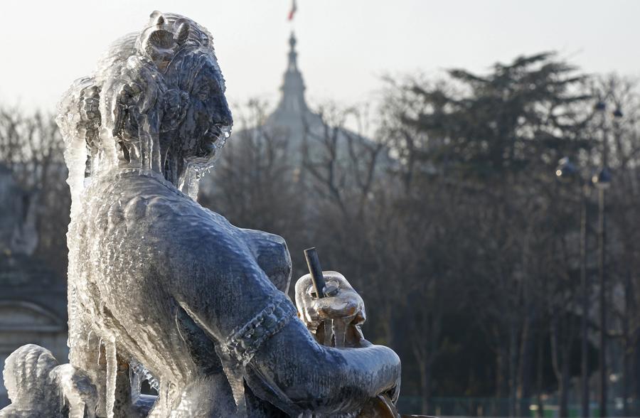 Статуя в фонтане покрытая льдом пляс де ла Конкорд в холодный зимний день, Париж, Франция, 20 января 2016.