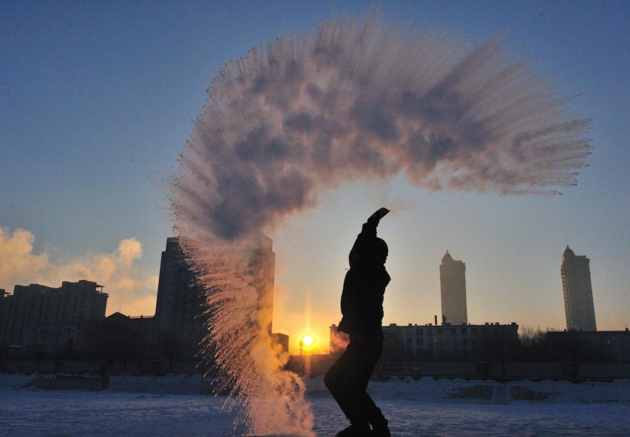 Мужчина выливает горящий чай при -40 °, стоя на замерзшей реке Сунгари в Харбине, Китай, 21 января 2016.