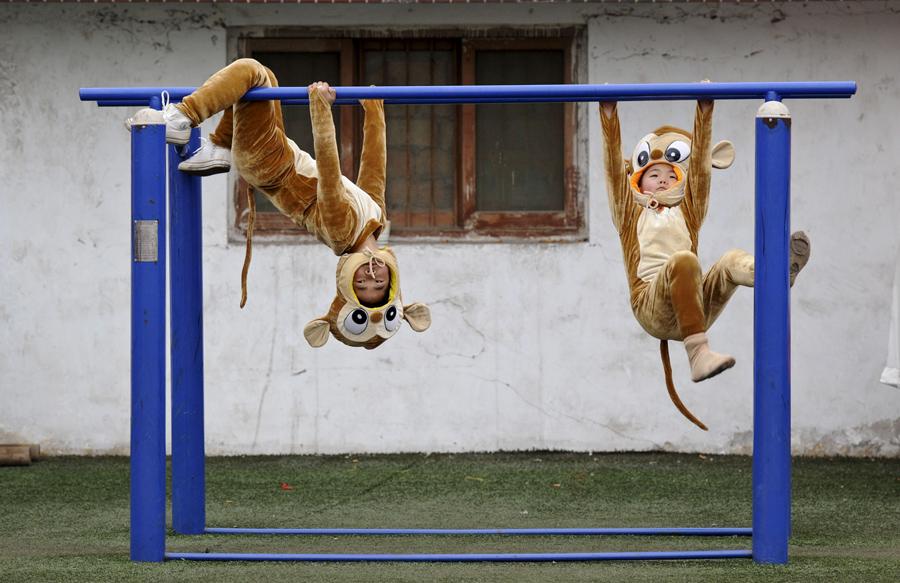 Дети одетые в костюмы обезьян играют перед выступлением на фестивале, перед Китайским новым годом по лунному календарю, в Ханьчэн провинции Шэньси, Китай, 16 января 2016.
