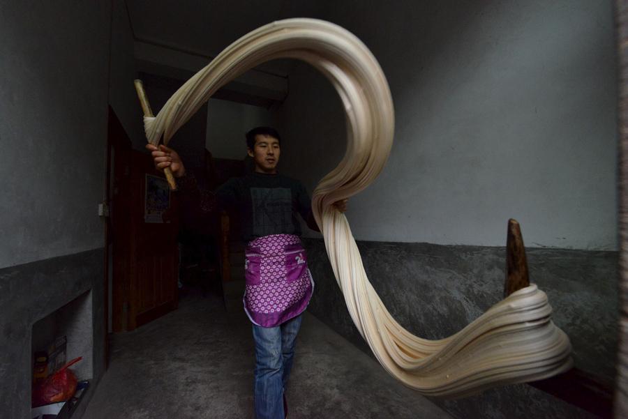 """Мужчина делает традиционные конфеты """"Матанг"""" в рамках подготовки к предстоящему китайскому новому году, Цзуньи, провинция Гуйчжоу, Китай, 18 января 2016."""
