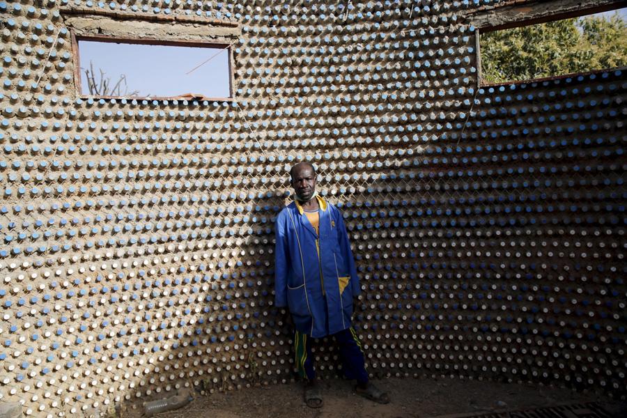 Человек стоит внутри дома построенного из одноразовых пластиковых бутылок на окраине Северной Нигерии городе Кадуна, 20 января 2016.