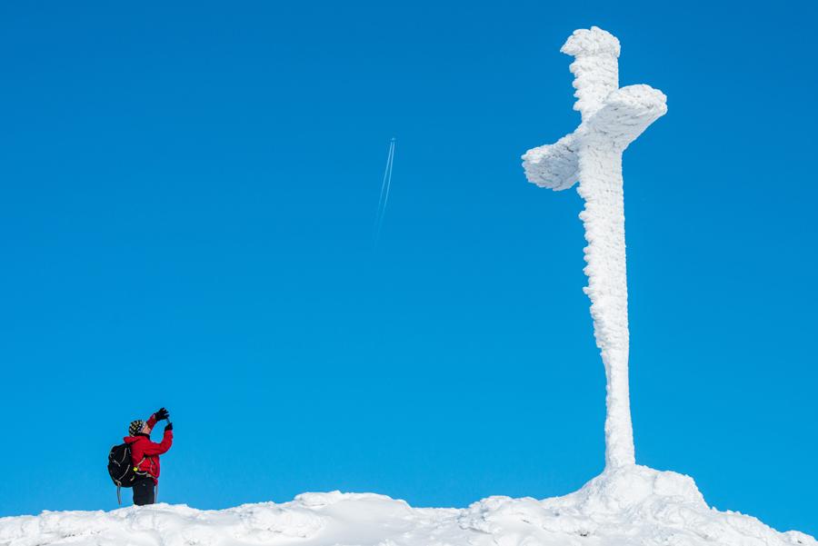 """Женщина фотографирует заснеженной """"Крест Саммит"""" на горе Гроссер Арбер возле Байериш-Айзенштайн, Германия, 21 января 2016."""