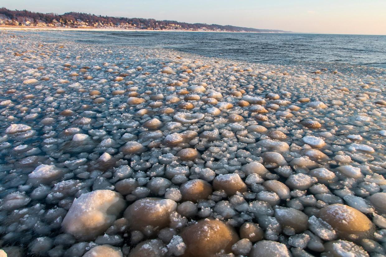 Ледяная корка на озере Мичиган и камни на пляже.