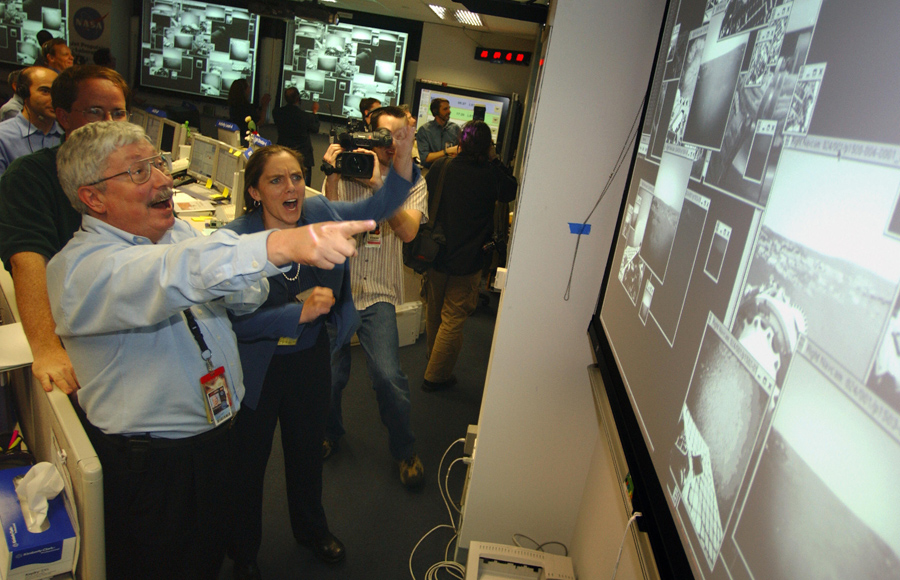 202 дней после запуска ракеты в день посадки - руководитель проекта Пит Тейсингер и менеджер Дженнифер Троспер реагируют как первые кадры прибывают в НАСА от марсохода «Оппортьюнити».