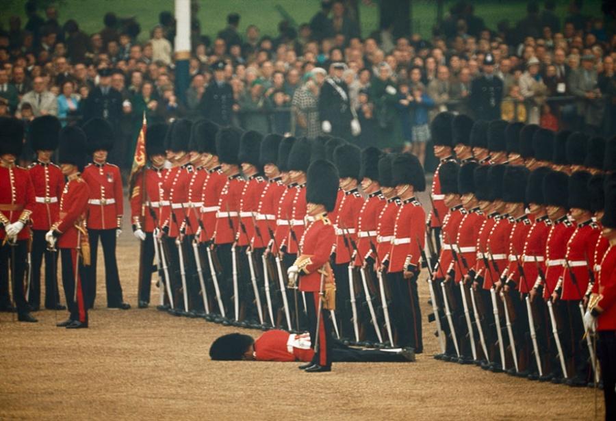 Несмотря на то что один из гвардейцев упал в обморок, остальные продолжают стоять по стойке смирно, Лондон, Англия, июнь 1966