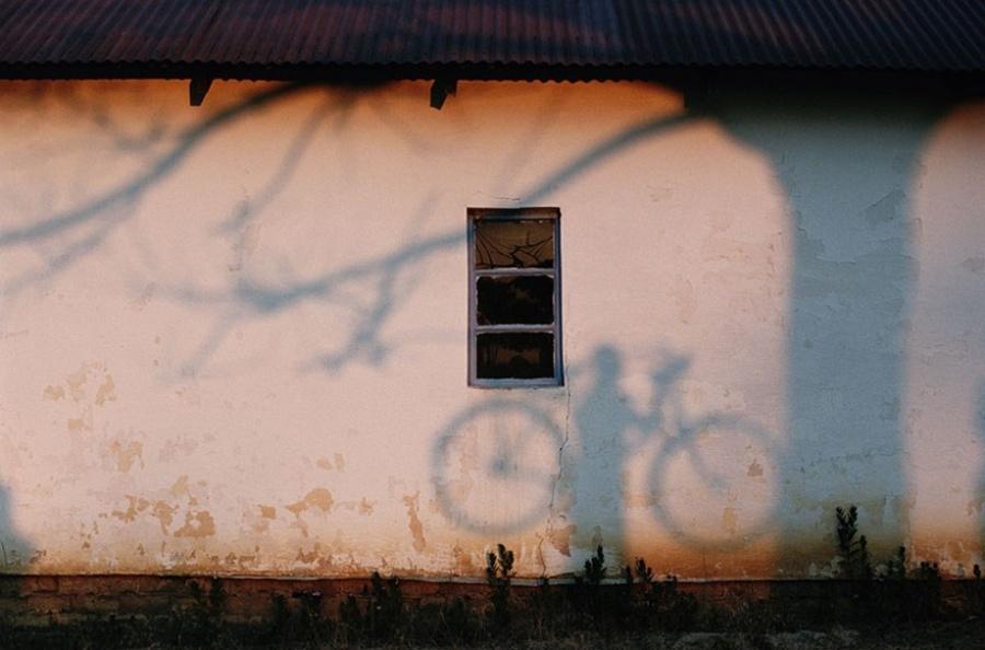 Тень человека с велосипедом на стене дома недалеко от реки Замбези, 1996