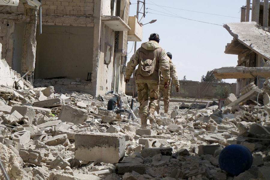 Сирийские войска идут по разрушенным улицам жилых районов современного города, прилегающих к древней Пальмире, после того как они отбили объект всемирного наследия ЮНЕСКО от ИГИЛ, 27 марта 2016.