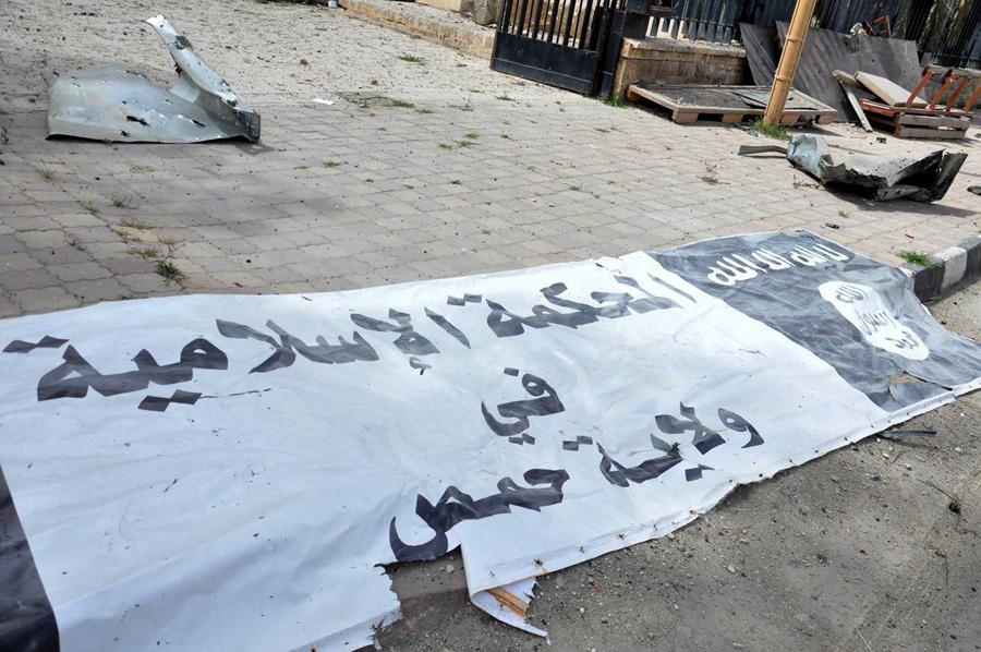 Баннер ИГИЛ лежит на земле после того, как силы президента Сирии Башара Аль-Асада отбили Пальмиру, 27 марта 2016.