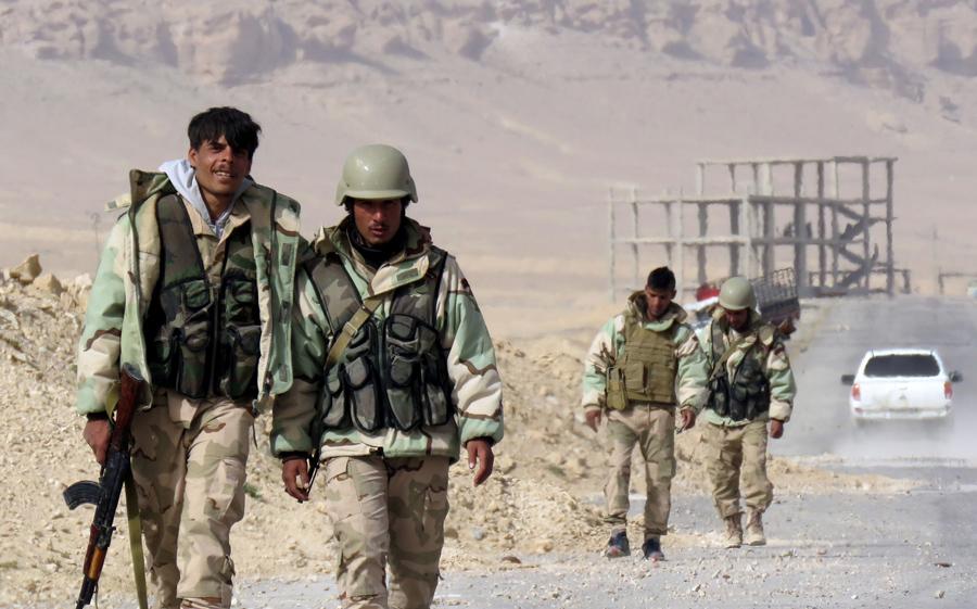 Сирийские правительственные силы идут по дороге на окраине Пальмиры 25 марта 2016, в ходе военной операции по освобождению древнего города.