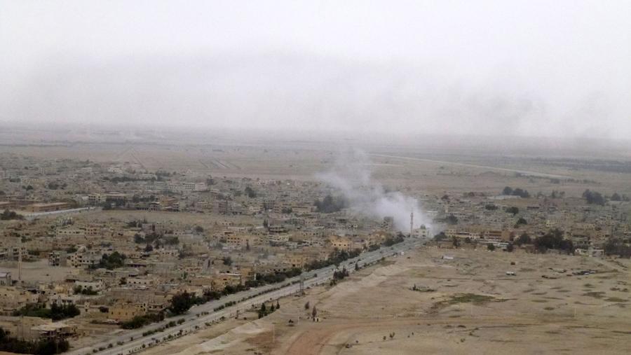 Снимок, сделанный 26 марта, 2016 года. Виден дым вздымающиеся над Пальмирой в ходе военной операции сирийских войск, чтобы отвоевать город от захватчиков исламского государства.