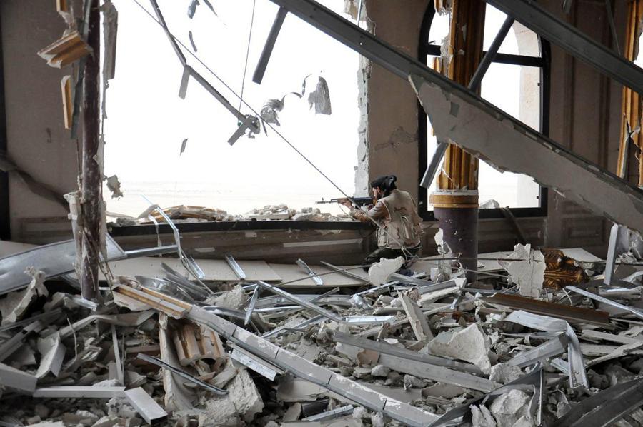 На этом фото, опубликованном в четверг 24 марта 2016 года, сирийский солдат занимает позицию внутри поврежденного дворца, у входа в Пальмиру.