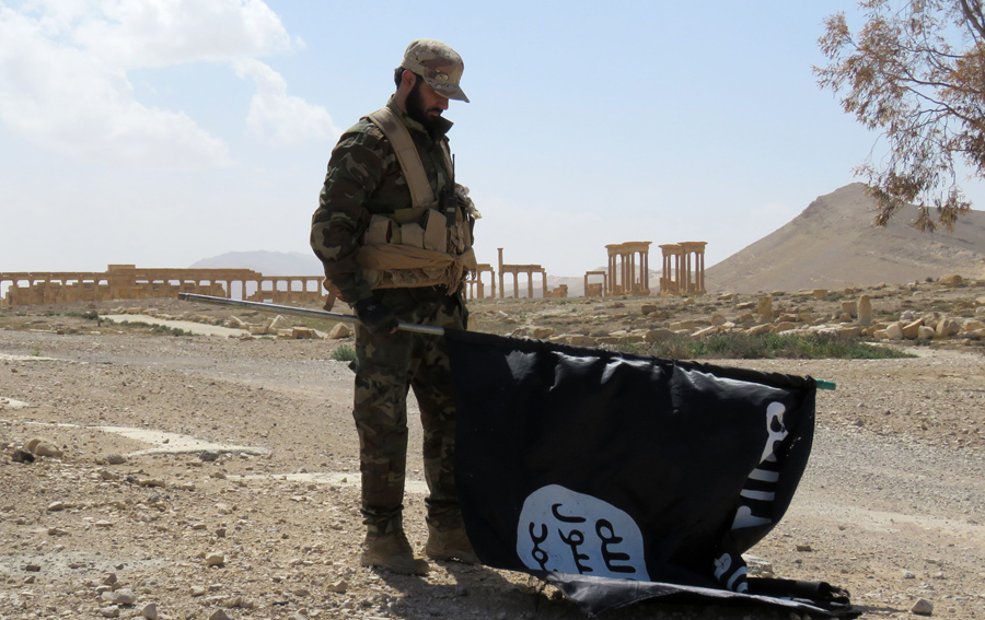 Член сирийских проправительственных сил несет флаг ИГИЛа у города Пальмира, 27 марта 2016, после того как войска отбили город.