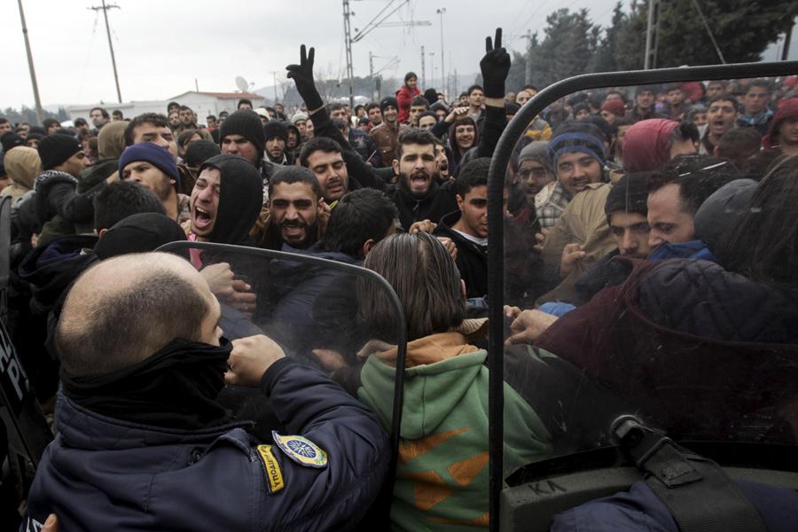 Беженцы и мигранты пытаются сломать греческий полицейский кордон, чтобы приблизиться к ограждениям на греко-македонской границе, недалеко от греческой деревни Идомени, 29 февраля 2016 года.