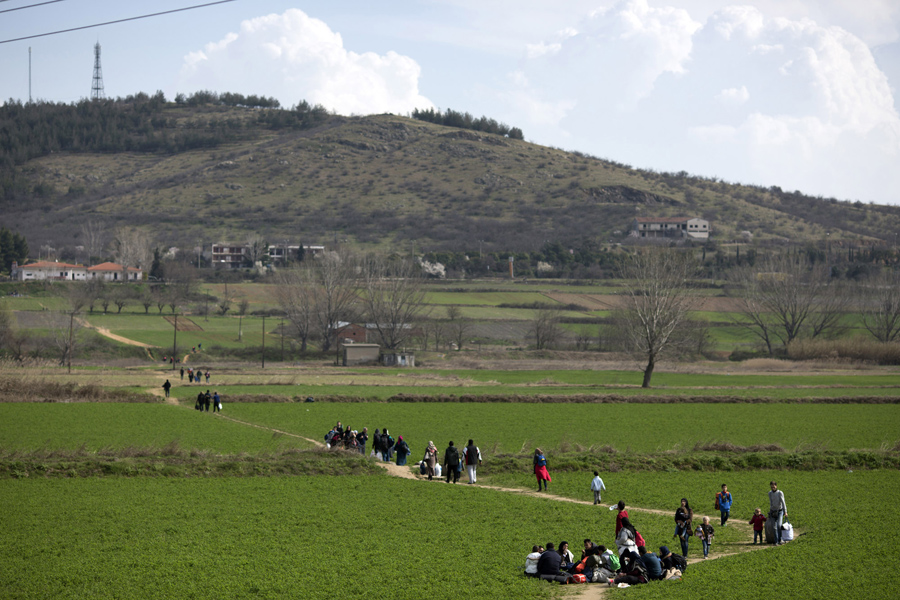 Семьи идут по полю к границе Греция-Македония, 2 марта 2016 года, в Идомени, Греция.