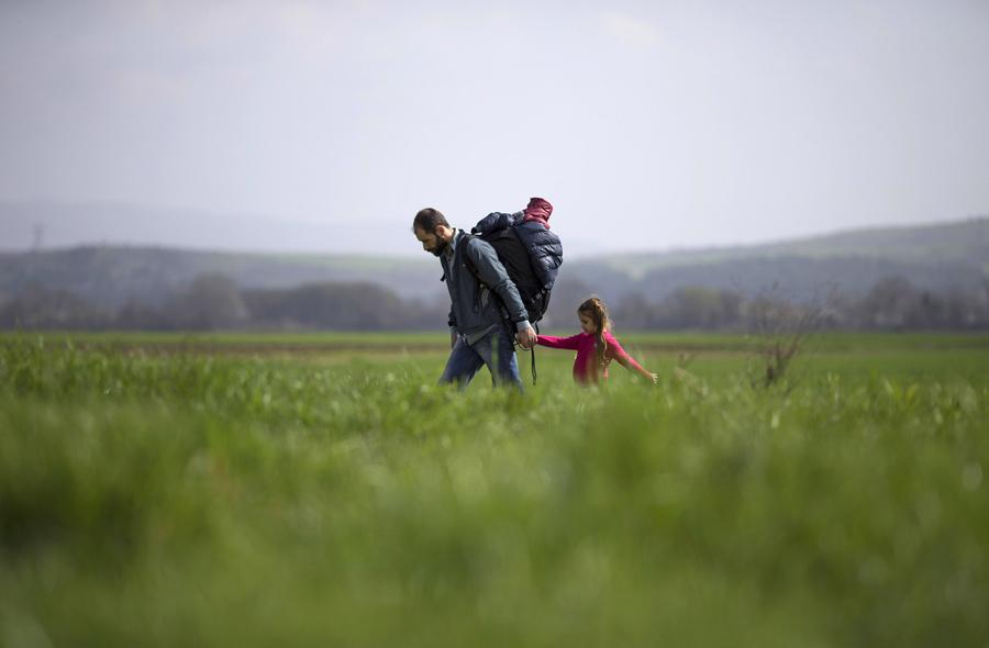 Мужчина держит за руку девочку и идут по полю к македонской границе.