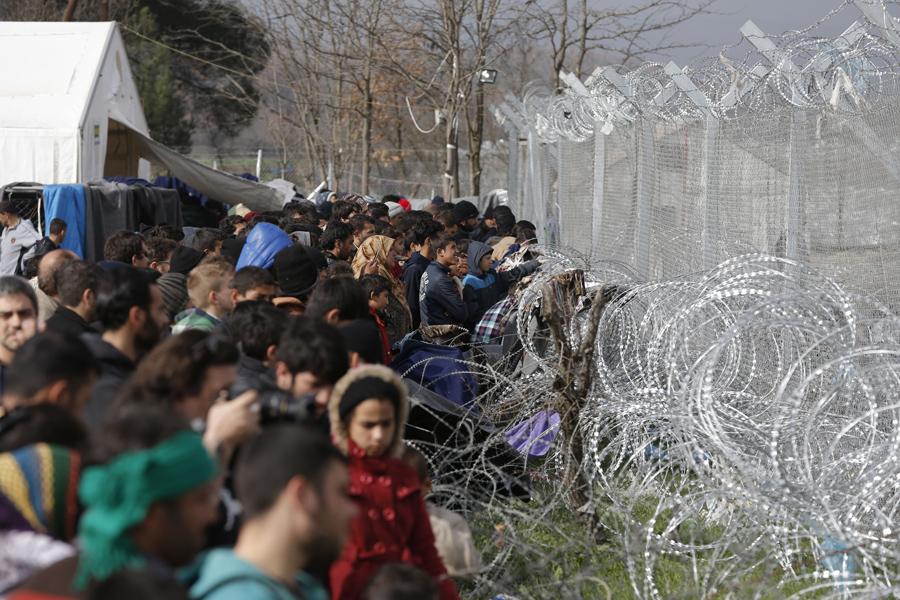Мигранты стоят рядом с забором греко-македонской границы, 1 марта 2016 года.