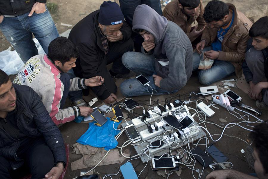 Мигранты заряжают свои мобильные телефоны от генератора, и ждут возможности пересечь границу в Македонии, в северной греческой пограничной станции Идомени 1 марта 2016 года.