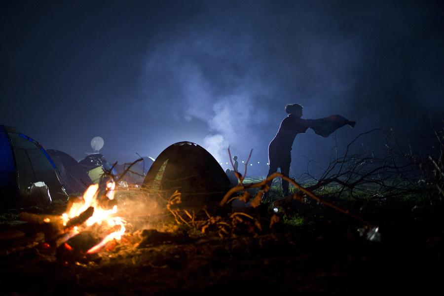 Женщина развешивает одежду рядом с палаткой в которой живут мигранты.