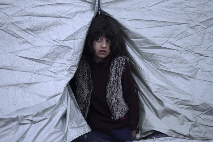 Девочка выглядывает из палатки, 1-го марта 2016 года.