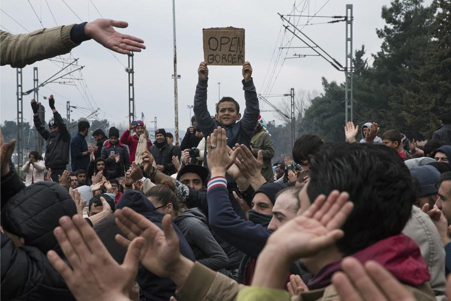 """Протестующие беженцы и мигранты блокируют железнодорожные пути на греко-македонской границе. Они скандируют """"открыть границу"""" в Идомени, Греции, 28 февраля 2016 года."""
