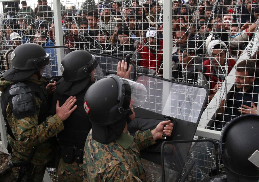 Беженцы и мигранты пытаются сломать забор на греческую границу, македонская полиция сдерживает их, возле южного македонского города Гевгелия, 29 февраля 2016 года.