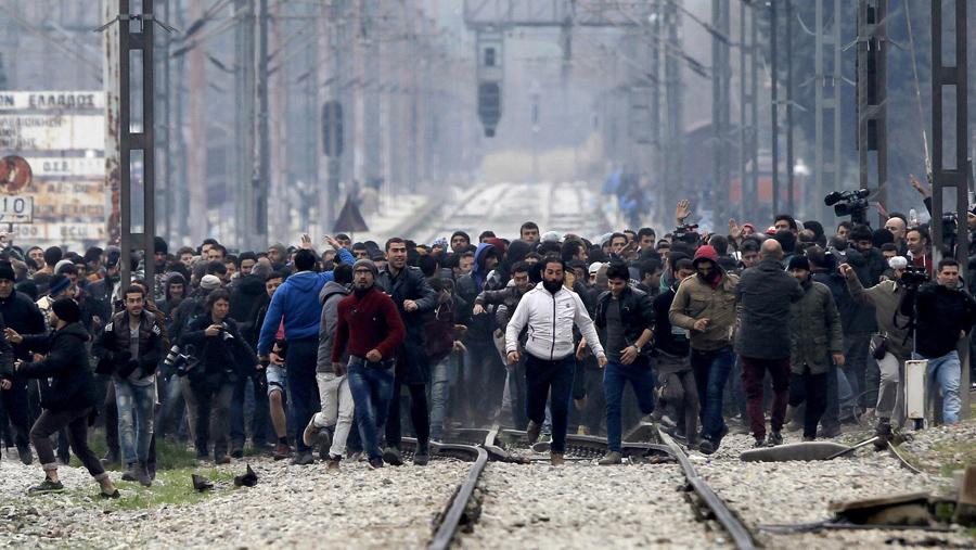 В этом снимке сделанном с македонской стороны, беженцы и мигранты в северной греческой деревни Идомени приближаются к греко-македонской границе, 29 февраля 2016 года.