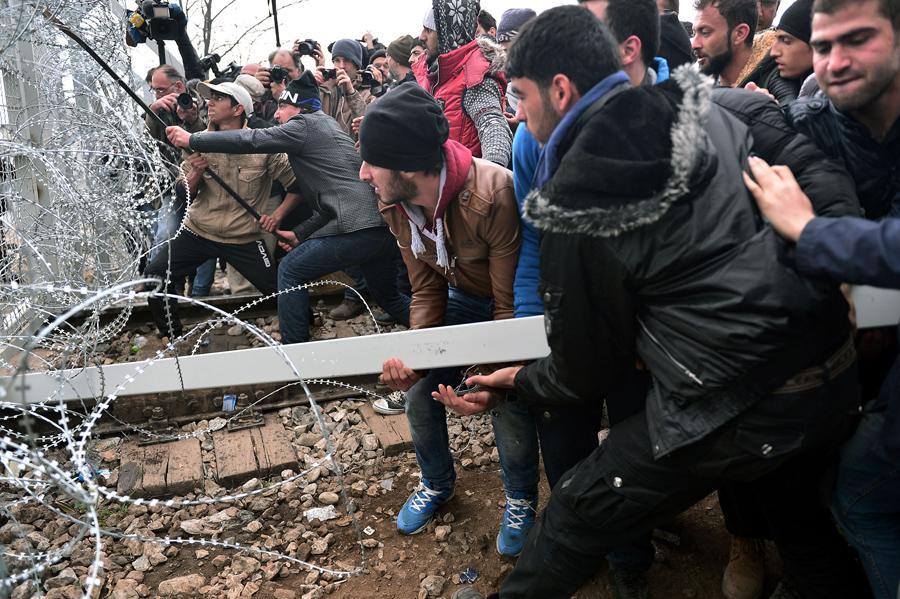 Мигранты пытаются прорваться через пограничный забор в Македонию близ городка Идомени, 29 февраля 2016 года.
