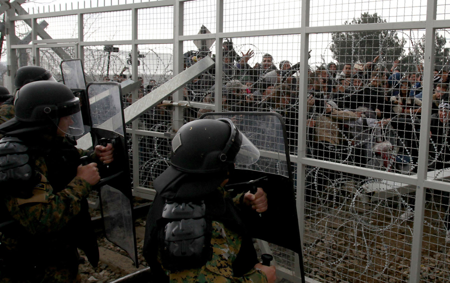 Беженцы и мигранты пытаются сломать забор на границе, македонские полицейские используют свои щиты для сдерживания, возле македонского города Гевгелия 29 февраля 2016 года.