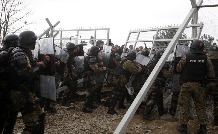 Мигранты пытаются прорваться через пограничный забор, македонская полиция толкает их обратно, возле Гевгелии, 29 февраля 2016 года.