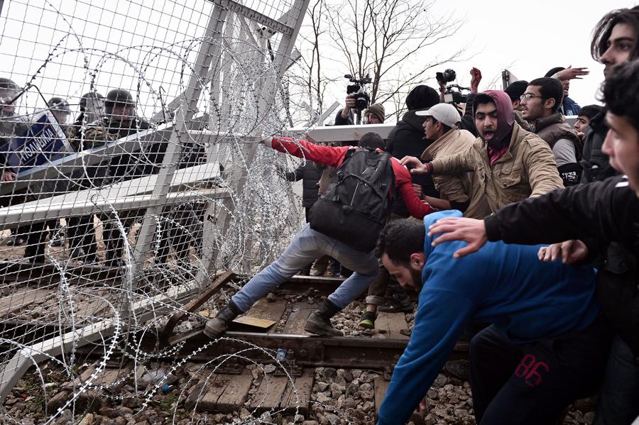 Мигранты пытаются прорваться через пограничный забор в Македонию около Идомени, 29 февраля 2016 года.