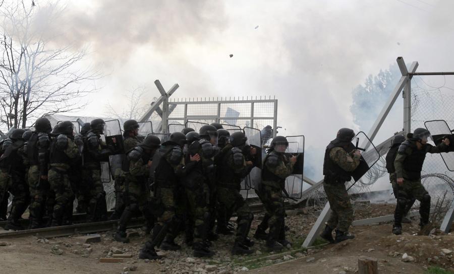 Приезжие разорвали пограничный забор и бросают камни с греческой стороны, македонские полицейские используют слезоточивый газ, 29 февраля 2016 года.