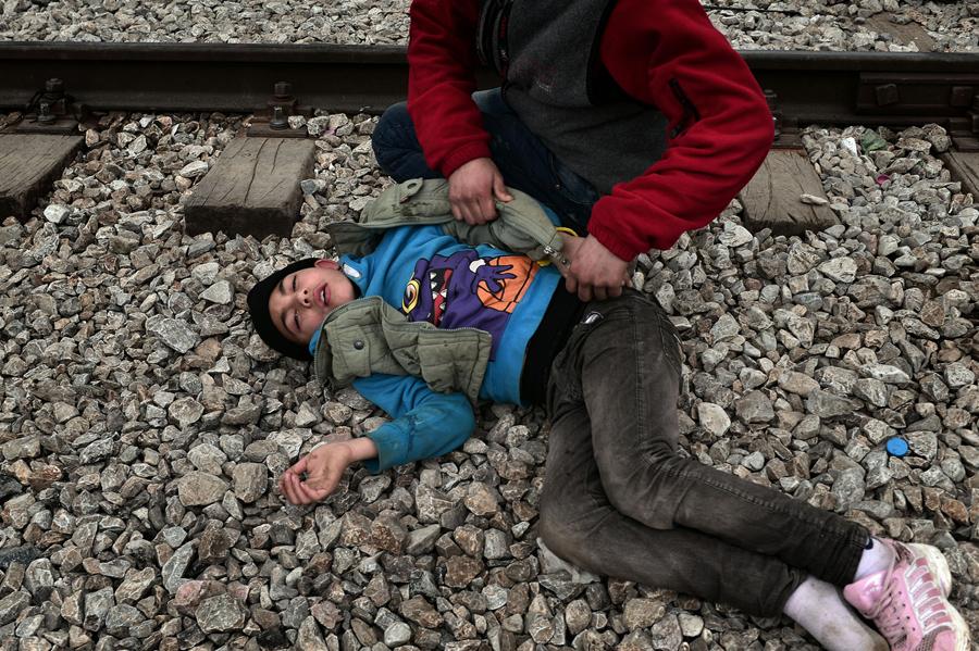 Мужчина помогает мальчику который упал после того как вдохнул слезоточивый газ. Македонская полиция применила слезоточивый газ на сотнях иракских и сирийских мигрантов, которые пытались прорваться через греческий пограничный забор в Идомени, 29 февраля 2016 года.