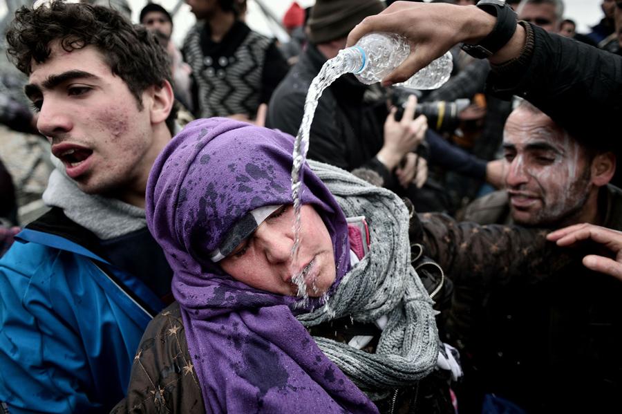 Беженец льет воду на лицо женщины, которая потеряла сознание после того как потеряла ребенка в панической толпе. Македонская полиция применила слезоточивый газ против беженцев в греко-македонской границе 29 февраля 2016 года.