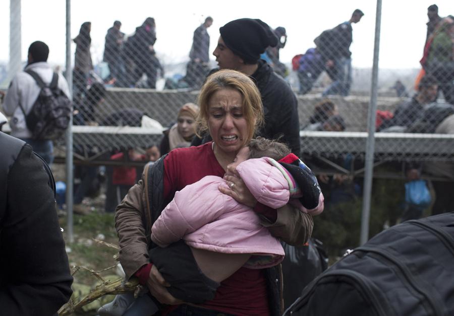 Женщина несет ребенка на греческой стороне границы, она убегает после того как македонская полиция применила слезоточивый газ, 29 февраля 2016 года.