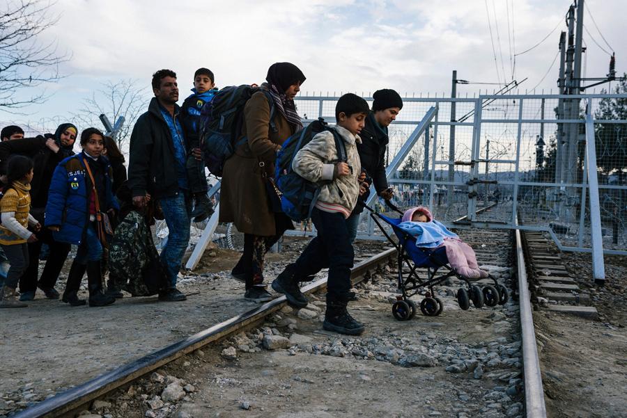 Беженцы пересекают греко-македонской границу в районе города Гевгелия 2-го марта 2016 года. Македония разрешила пустить около 250 мигрантов, более 10000 остались ждать в жалких условиях греческих чиновников и журналистов AFP.