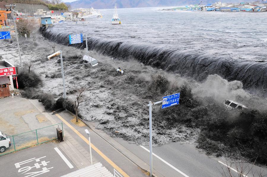 Цунами достигло города Мияко пробив дамбу и затопив улицы в префектуре Иватэ, Япония, после землетрясения магнитудой 9,0, 11 марта 2011 года.