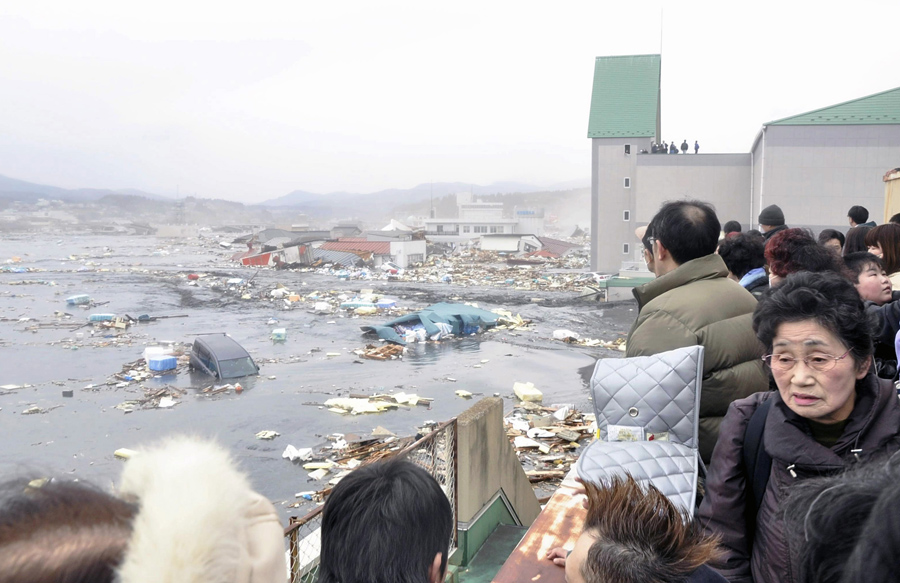 Люди смотрят на последствия цунами после землетрясения в городе Кесеннума, префектура Мияги, 11 марта 2011 года.