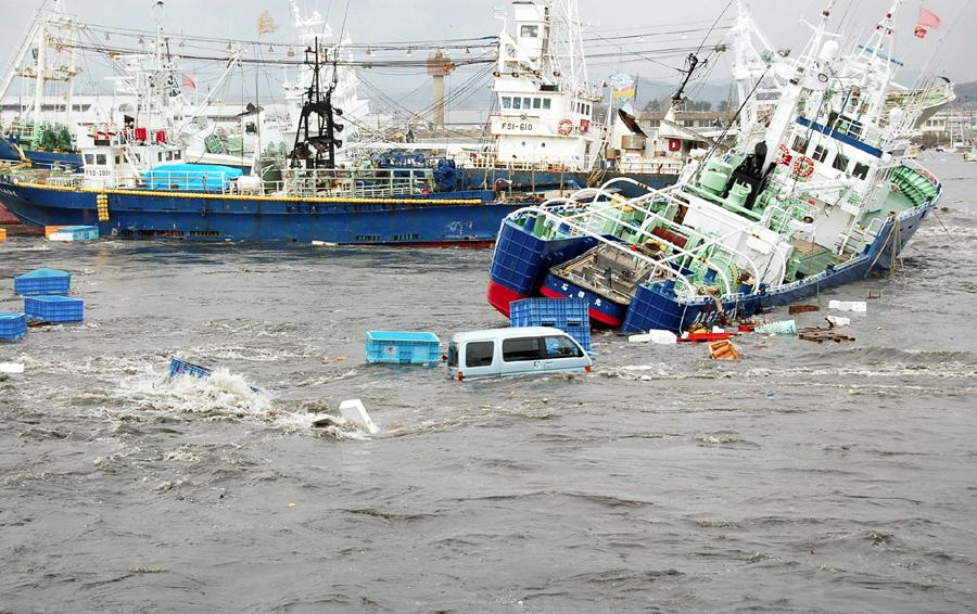 Рыбацкие лодки и корабли повреждаются волнами цунами в порту Онахама города Иваки, Северной Японии 11 марта 2011 года.