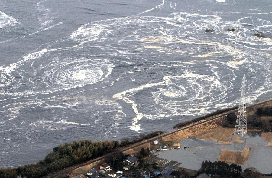 Водовороты говорят очледующих цунами и землетрясениях в городе Иваки, префектура Фукусима, 11 марта 2011 года.