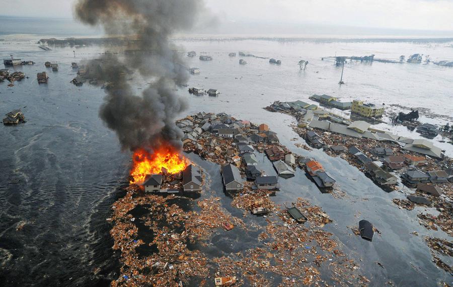 Дома в огне после землетрясения и цунами в городе Натори на северо-востоке Японии, 11 марта 2011 года.