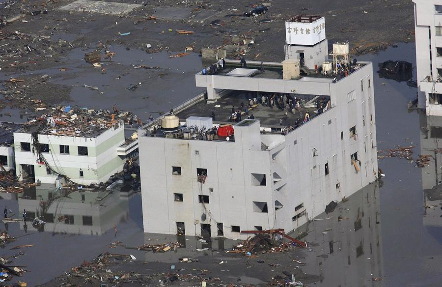 Люди спасаются на крыше здания в поселке Минамисанрику, Мияги, Япония после катастрофического землетрясения и цунами.